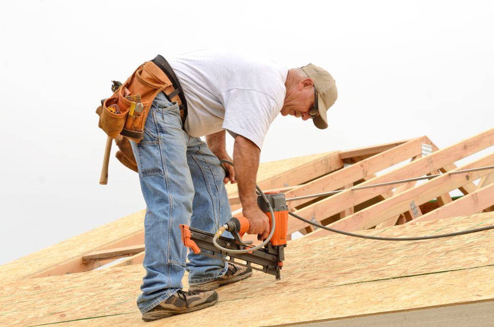 roofer drilling on the roof